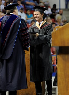President Les Guice presents a diploma to a summer quarter graduate.