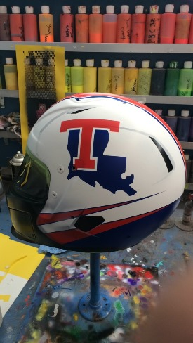 Driver's helmet being painted to resemble Louisiana Tech football helmet