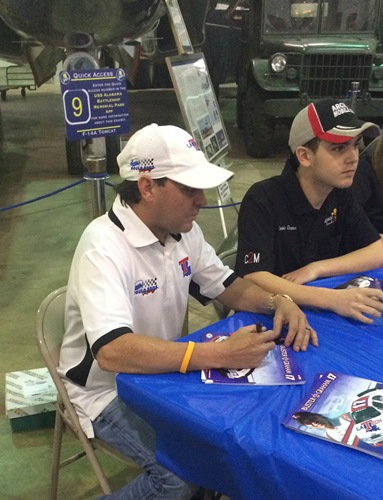 Buster Graham signs autographs for race fans on board the USS Alabama.