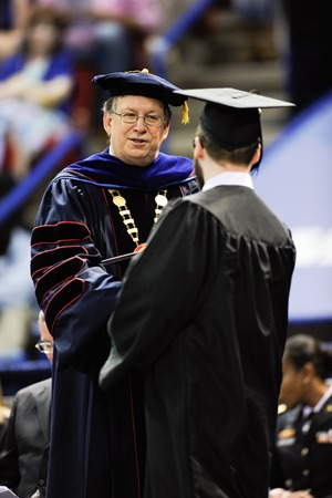 Louisiana Tech President Les Guice congratulates a new graduate during spring commencement.