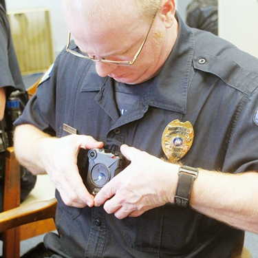 Louisiana Tech University Police Cpl. Allen Carnahan places his new department-issue body camera on his uniform. Tech police are now wearing the palm-sized cameras.  Photo courtesy of Ruston Daily Leader.