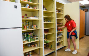 A student helps organize food at the Food Pantry.