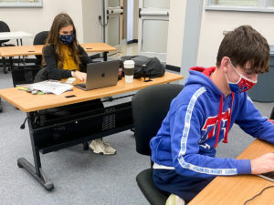 Students in a classroom and engaging in online debate contest.