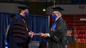 Joe Bates receives his diploma from Dr. Les Guice.