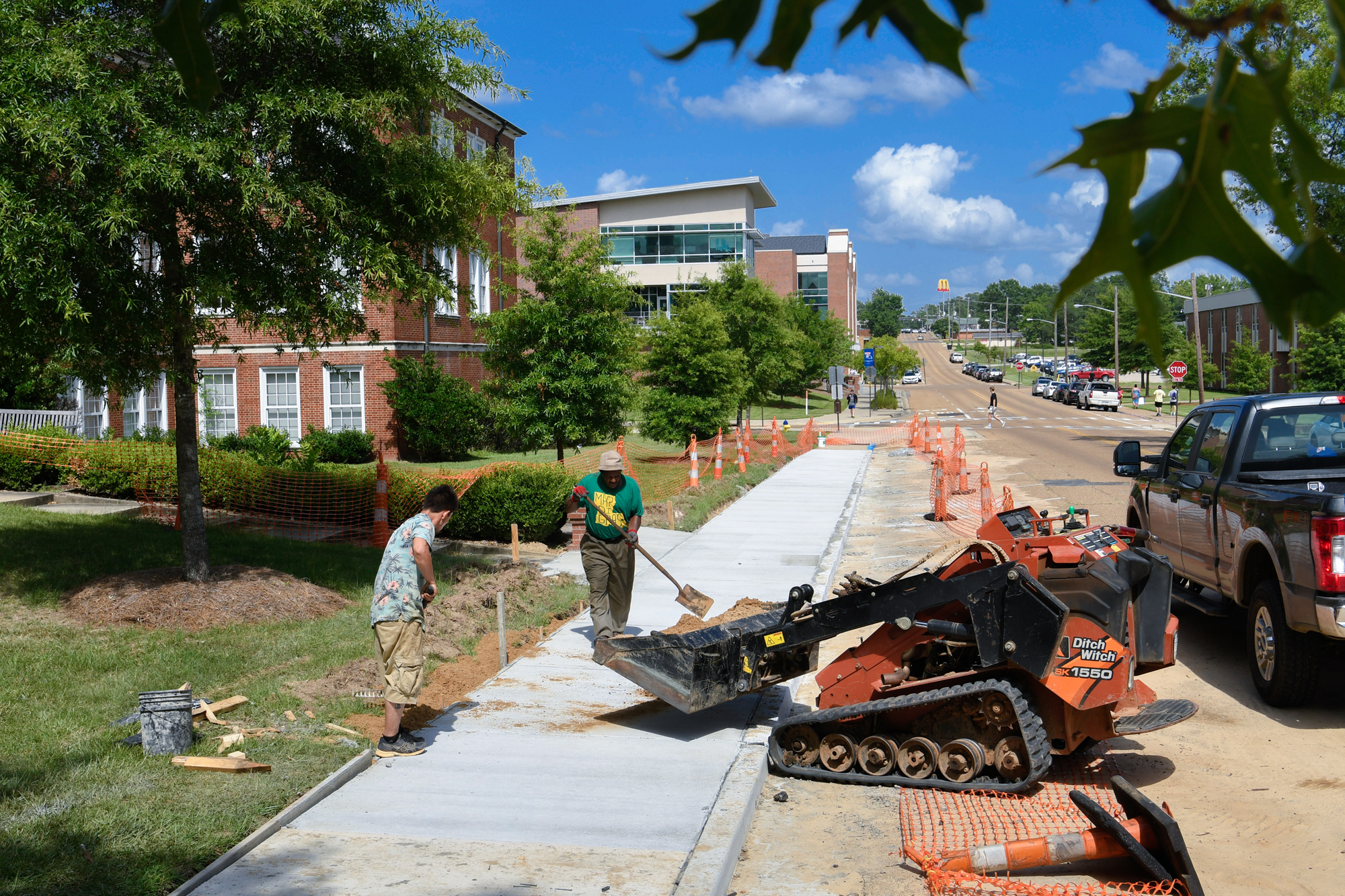 Construction workers shovel dirt to fill in the gaps around newly poured concrete walkways in front of Bogard Hall.